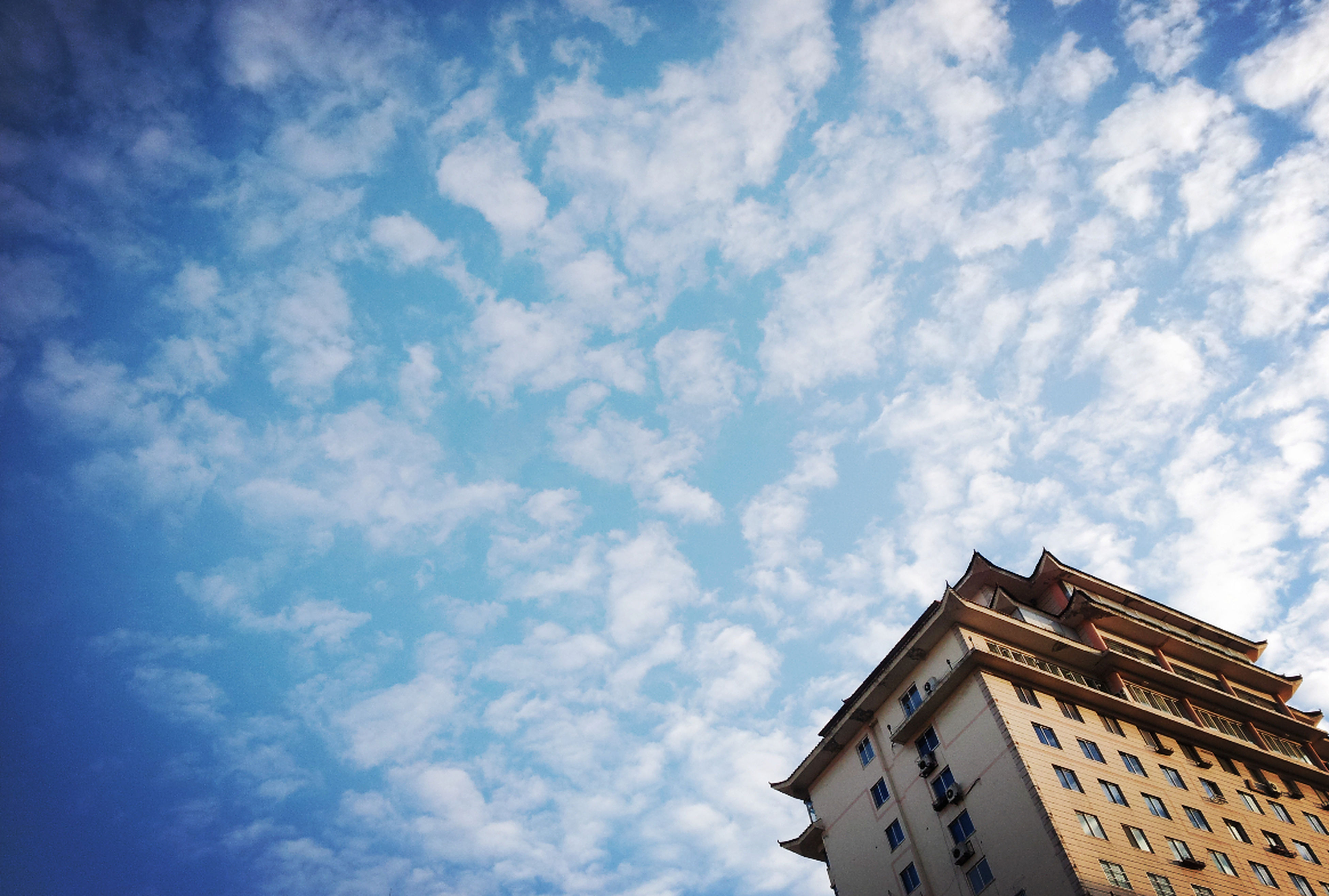 low angle view, architecture, building exterior, built structure, sky, cloud - sky, cloud, blue, cloudy, building, high section, day, outdoors, city, no people, residential building, residential structure, nature, directly below, window