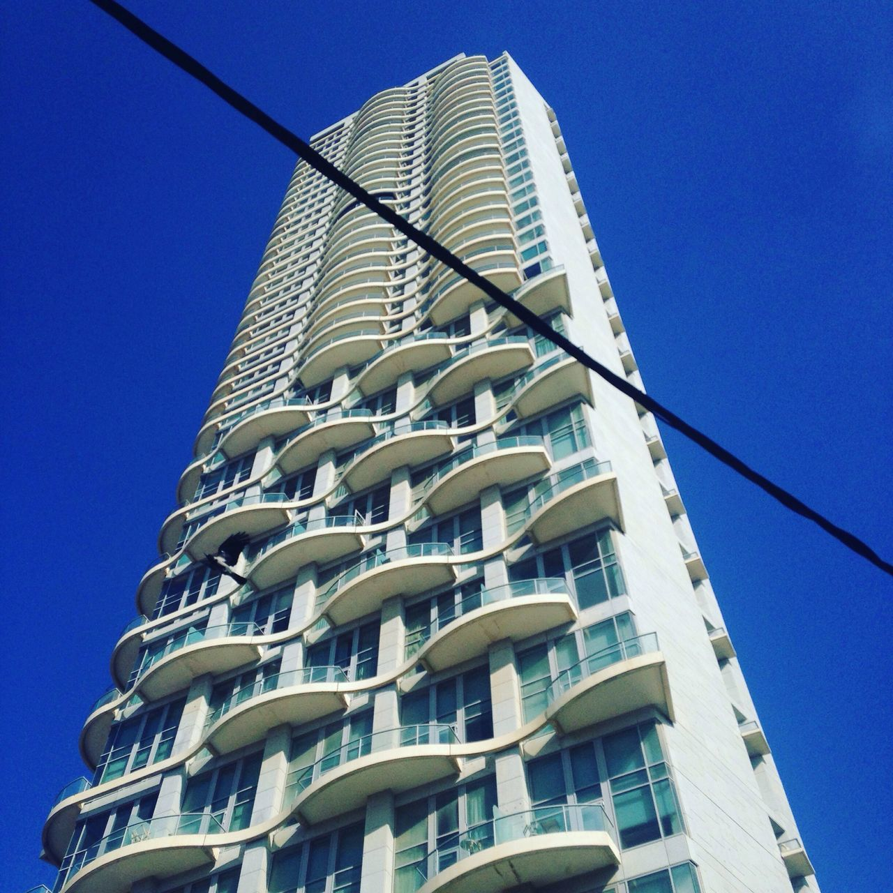architecture, low angle view, building exterior, built structure, window, clear sky, blue, day, balcony, modern, no people, residential building, skyscraper, outdoors, apartment, city, sky