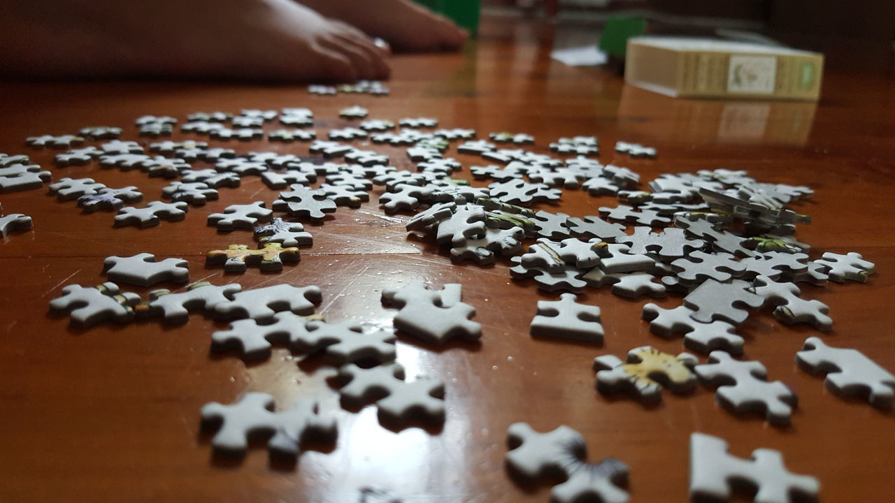 jigsaw piece, jigsaw puzzle, puzzle, high angle view, table, indoors, leisure games, strategy, large group of objects, solution, close-up, no people, day