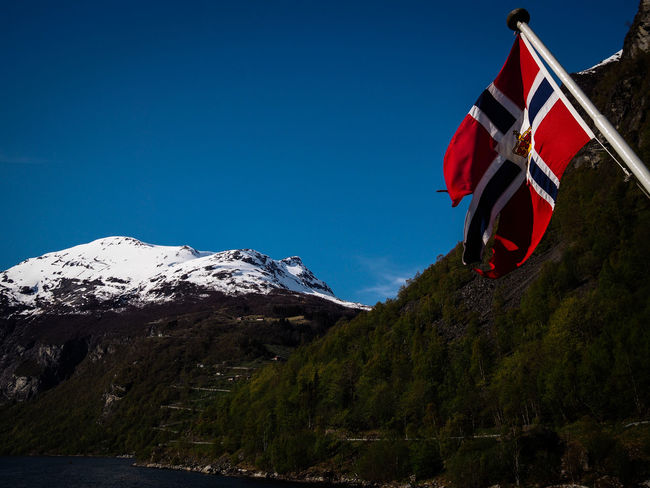 Spring at Geirangerfjord on a ferry Adventure Blue Sky Boat Boats Famous Place Ferry Fjord Fjords Flag Flags Geiranger Geirangerfjord Landmark Landscape Mountain Mountain Range Norway On A Boat Outdoors Road Ship Landscapes With WhiteWall Travel Traveling Travelling