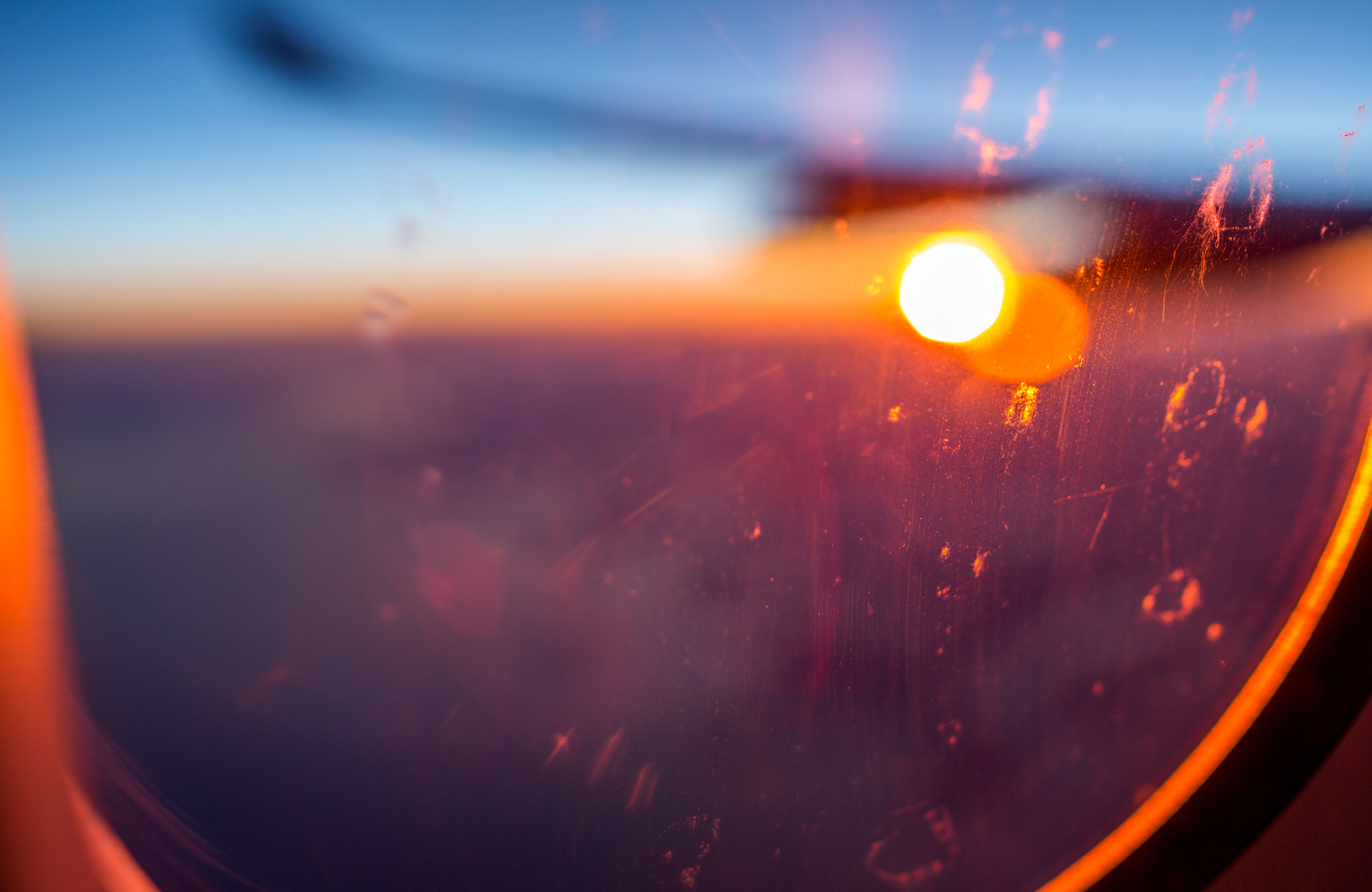 sunset, airplane, transportation, mode of transport, sun, travel, glass - material, transparent, air vehicle, window, scenics, landscape, beauty in nature, lens flare, nature, sky, flying, aerial view, cloudscape, orange color, focus on foreground, outdoors, cloud - sky, vibrant color, journey, tranquil scene