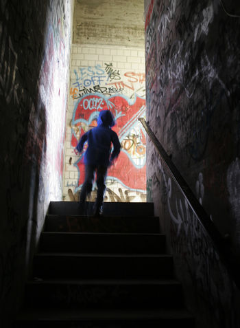 Boy Boy Running Bright Built Structure Full Length Graffiti Hoddy Indoors  Light And Shadow Light At The End Of The Tunnel Old Buildings Railing Running Running Away Running Up Stairs Scape Staircase Steps Steps And Staircases Wall - Building Feature Telling Stories Differently