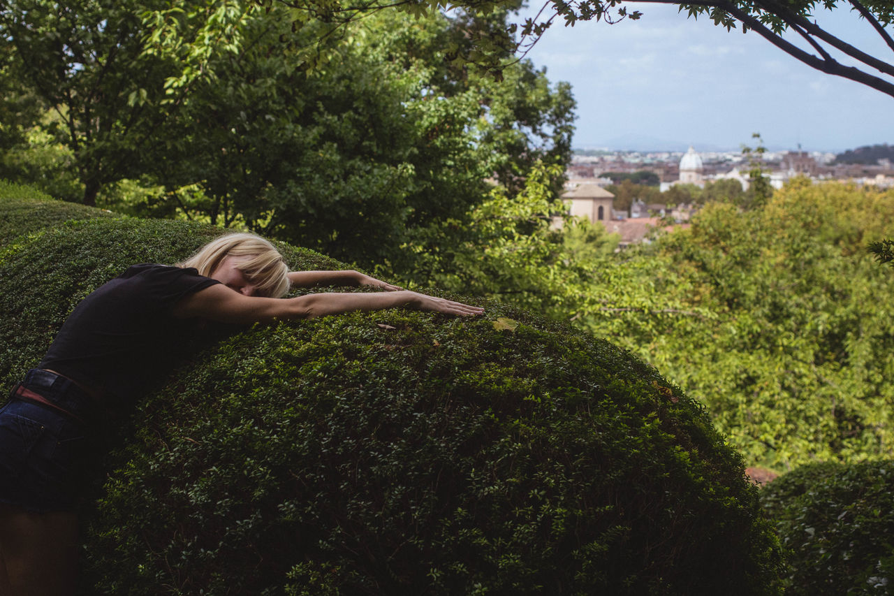 tree, grass, day, one person, young adult, young women, outdoors, real people, nature, growth, architecture, building exterior, one young woman only, sky, blond hair, people