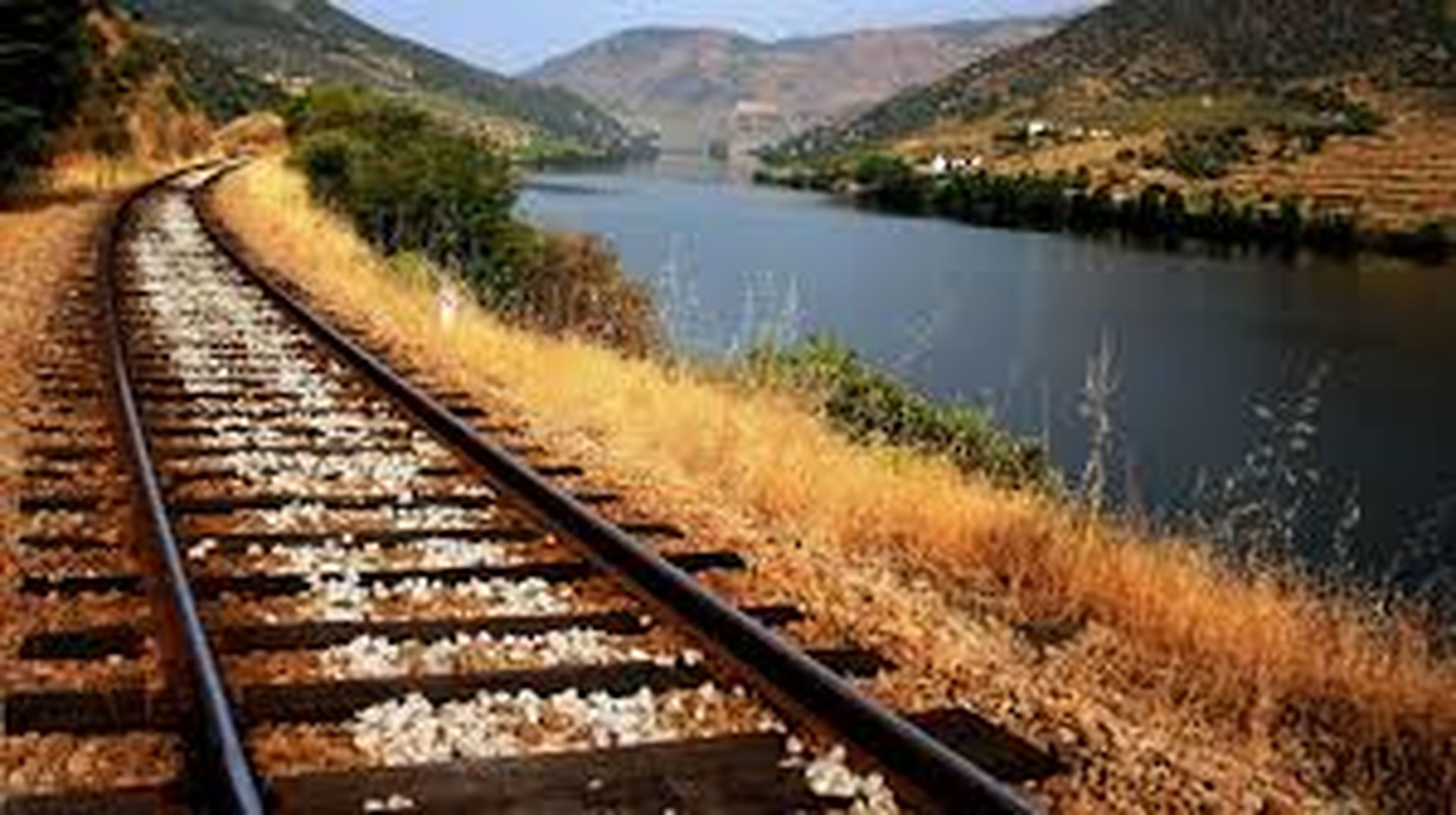 railroad track, rail transportation, transportation, mountain, water, railway track, public transportation, high angle view, railing, connection, nature, tranquility, river, tranquil scene, landscape, train - vehicle, mountain range, train, day, no people