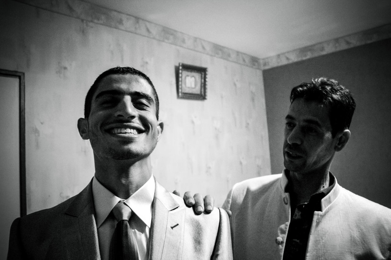 two people, young men, real people, businessman, well-dressed, suit, indoors, full suit, young adult, smiling, headshot, togetherness, love, men, happiness, day, bonding, friendship, groom, people
