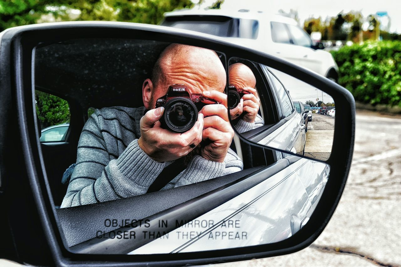 car, real people, transportation, photographing, one person, leisure activity, headshot, technology, lifestyles, human hand, land vehicle, mature men, side-view mirror, photography themes, day, photographer, men, camera - photographic equipment, outdoors, portrait, close-up, people
