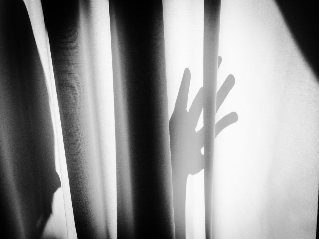 Shadow Of Human Hand On White Curtain