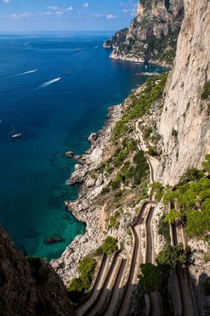 Capri, Italy, Via Krupp winds along the slope, leading to the sea underneath. Beauty In Nature Blue Capri Cliff Cliffs Geometric Architecture Holiday Italy Krupp Landscape Lines Mountain Panorama Path Pathway Rock Formation Sea Seascape Traveling Vacations Vía Krupp Walkway Water