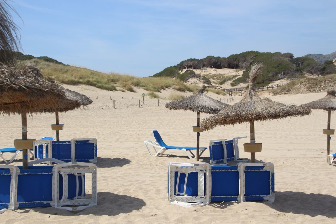 beach, sand, beach umbrella, nature, thatched roof, sun lounger, shore, summer, sea, day, beauty in nature, sunlight, outdoors, absence, scenics, chair, sky, tranquility, tranquil scene, shelter, vacations, water, canopy, shadow, no people, blue, arid climate, sand dune, seat, clear sky
