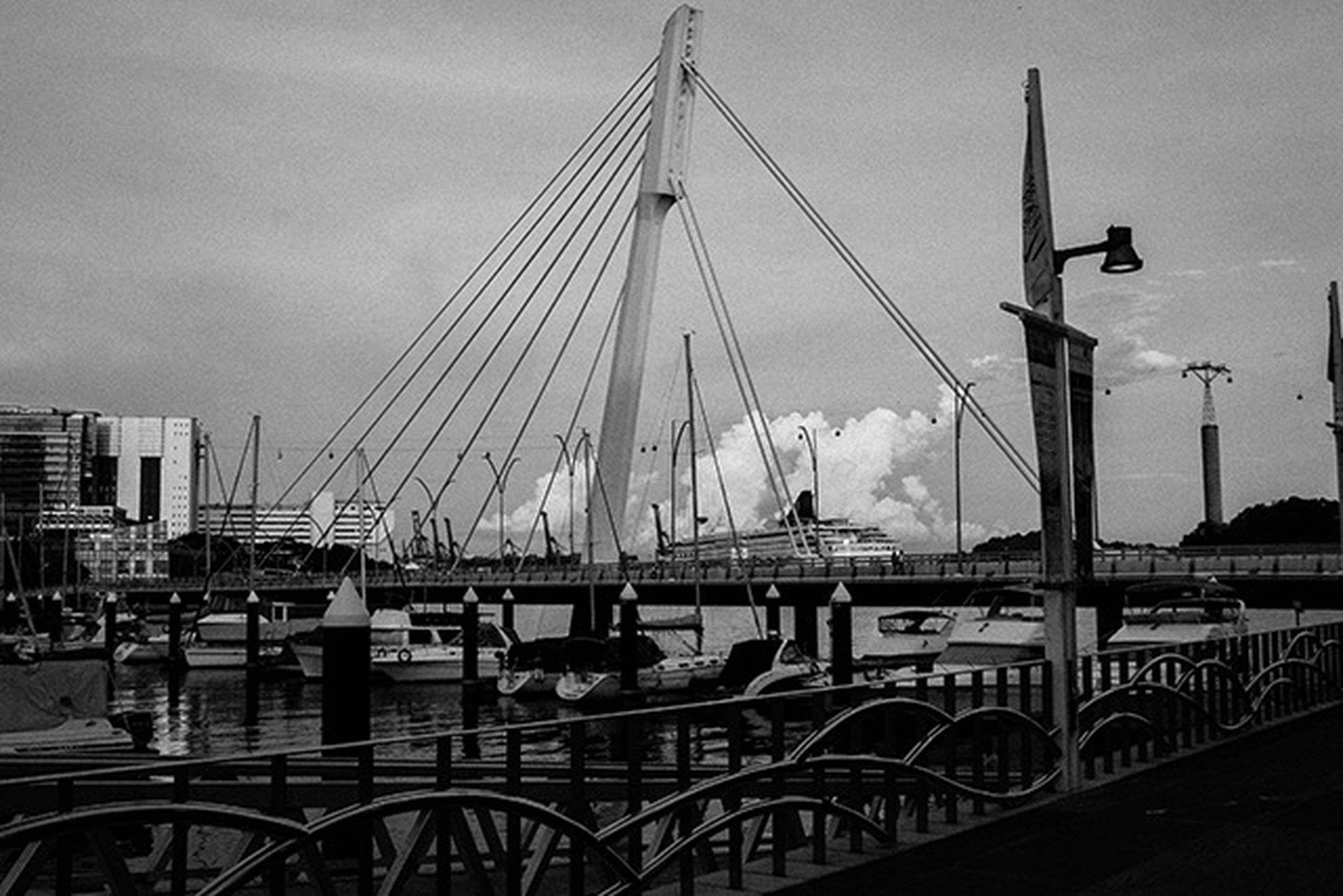 transportation, bridge - man made structure, connection, mode of transport, built structure, sky, architecture, nautical vessel, water, engineering, river, bridge, suspension bridge, railing, boat, travel, cable-stayed bridge, city, outdoors, street light
