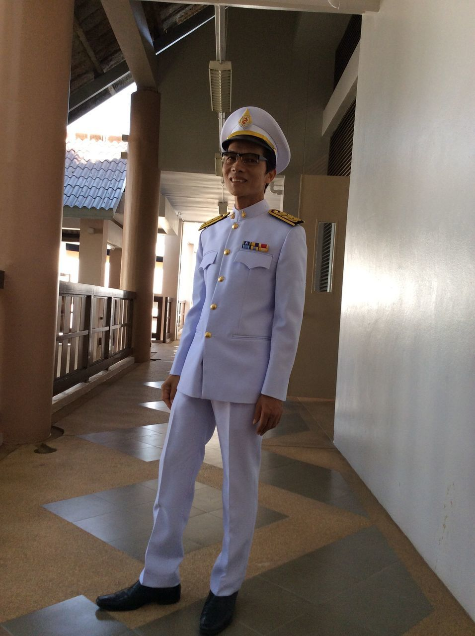 young adult, one person, standing, real people, looking at camera, uniform, full length, portrait, indoors, young men, front view, leisure activity, lifestyles, day, architecture