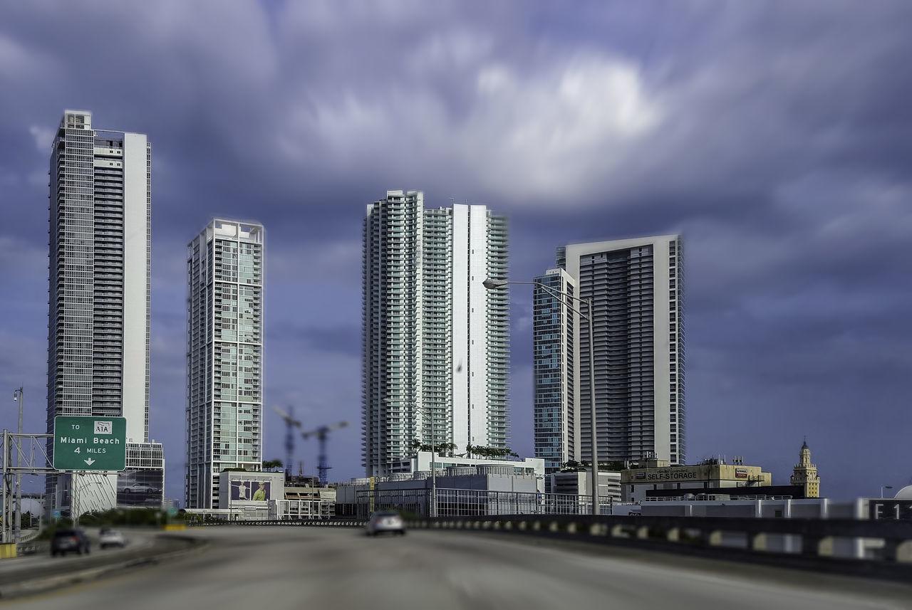 architecture, built structure, building exterior, skyscraper, modern, city, cloud - sky, sky, outdoors, day, cityscape, bridge - man made structure, no people, travel destinations, urban skyline