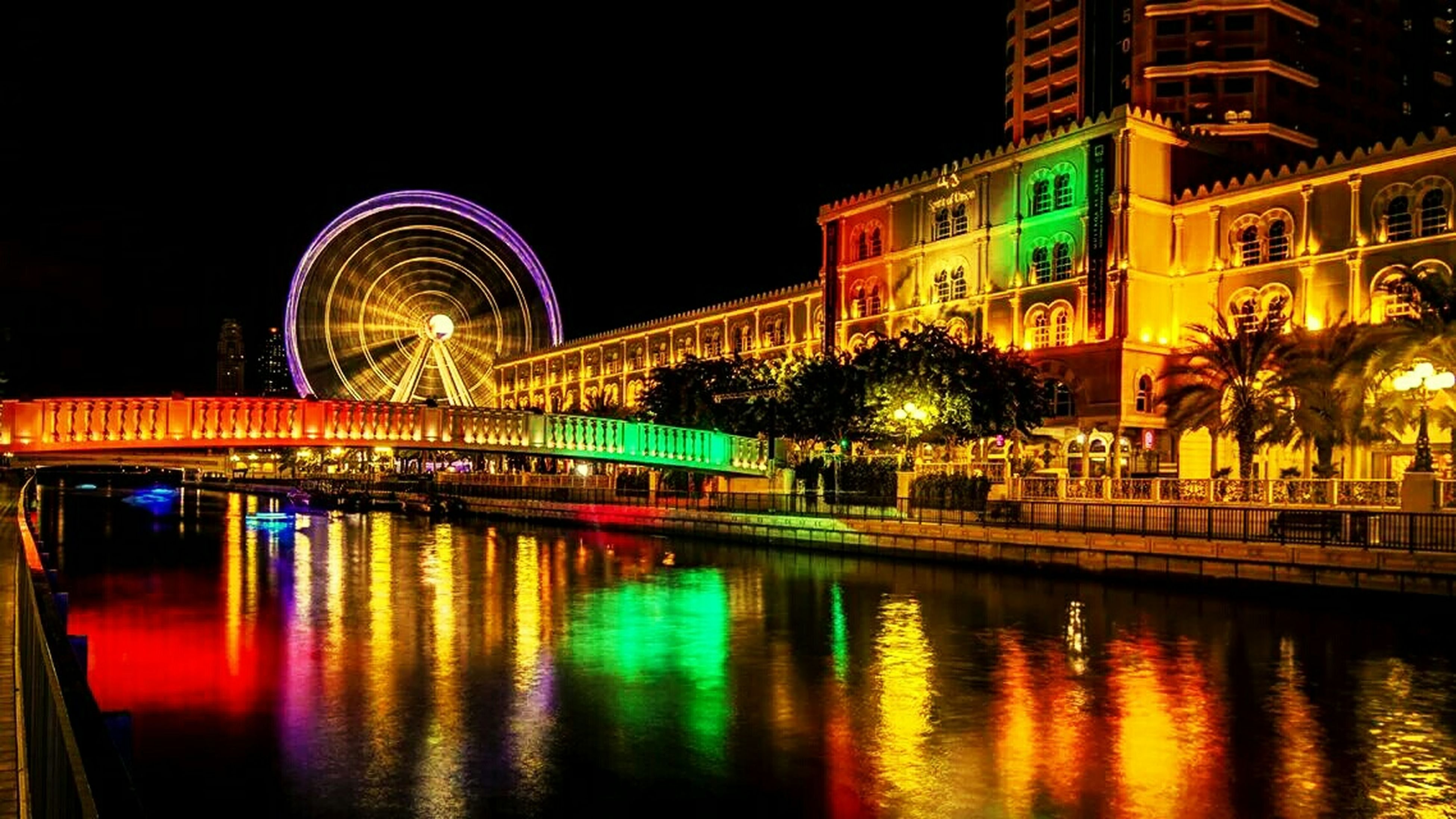 illuminated, night, architecture, building exterior, built structure, reflection, water, city, waterfront, long exposure, multi colored, motion, river, light trail, outdoors, city life, ferris wheel, travel destinations, light - natural phenomenon, blurred motion