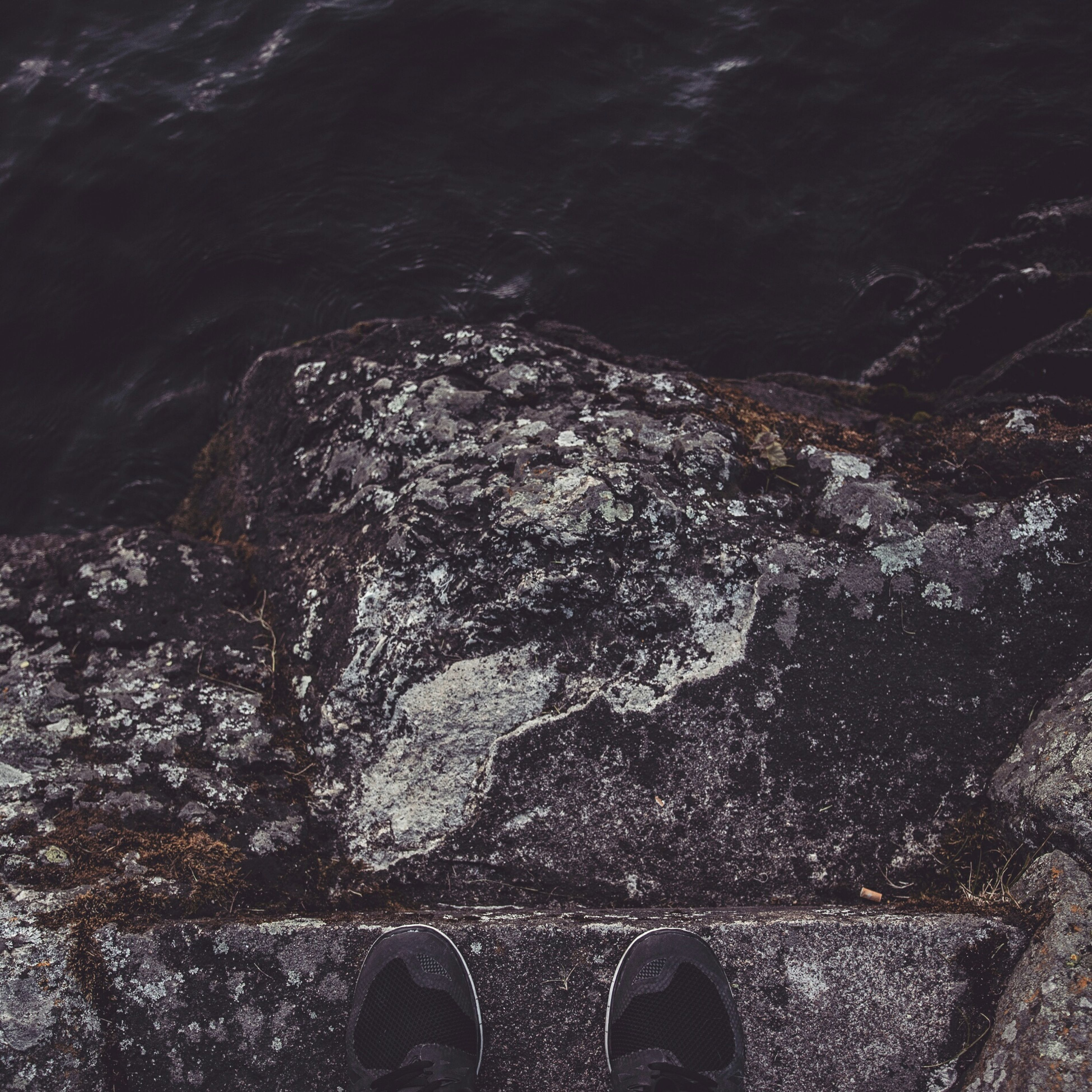 water, high angle view, low section, rock - object, person, personal perspective, outdoors, day, shoe, sea, river, unrecognizable person, transportation, part of, built structure, nature, architecture, reflection