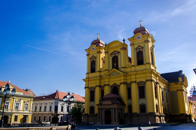 Architecture Blue Building Exterior Built Structure Church Cloud Day Façade Low Angle View Outdoors Piazza Place Of Worship Religion Romania Sky Spirituality Square Travel Destinations Yellow