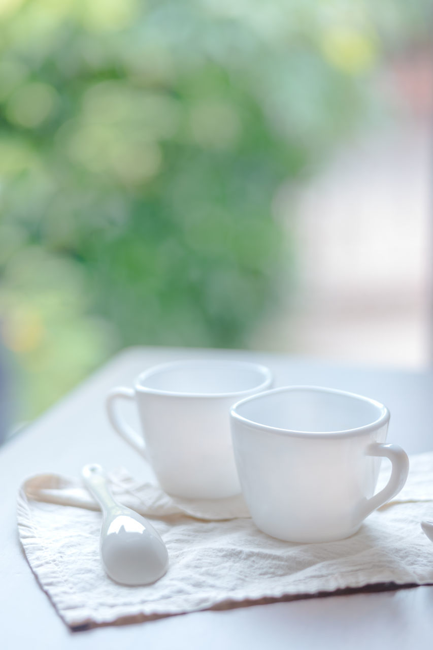 Close-Up Of Spoon With Coffee Cups On Napkin At Table
