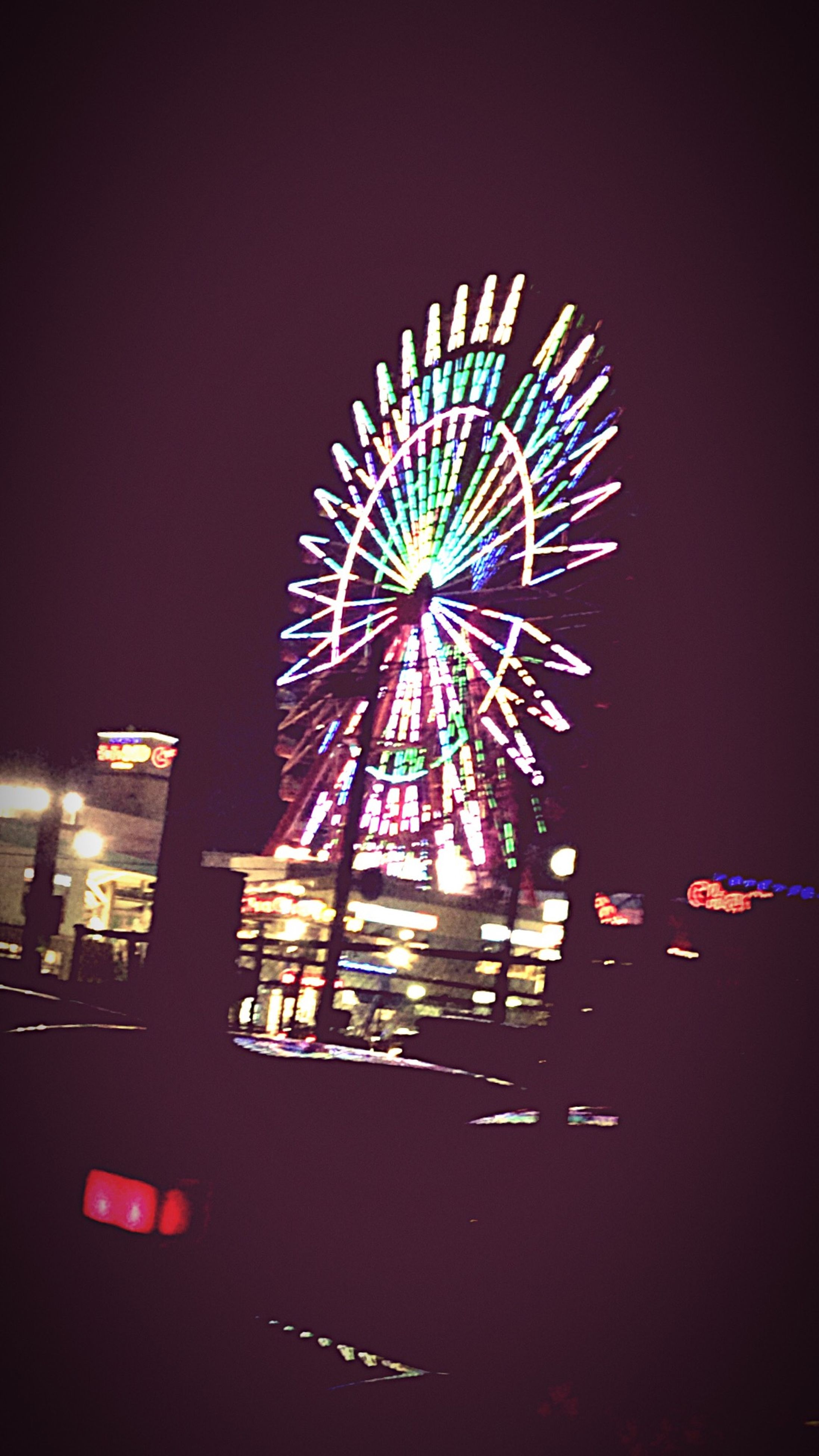 illuminated, night, arts culture and entertainment, low angle view, multi colored, ferris wheel, amusement park, amusement park ride, celebration, glowing, architecture, built structure, sky, lighting equipment, long exposure, motion, firework display, building exterior, clear sky, decoration