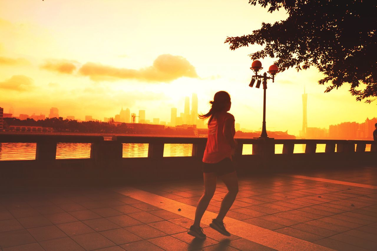 sunset, full length, real people, one person, river, tree, railing, leisure activity, sky, lifestyles, architecture, city, outdoors, silhouette, built structure, women, water, building exterior, young women, cityscape, nature, beauty in nature, young adult, day, people