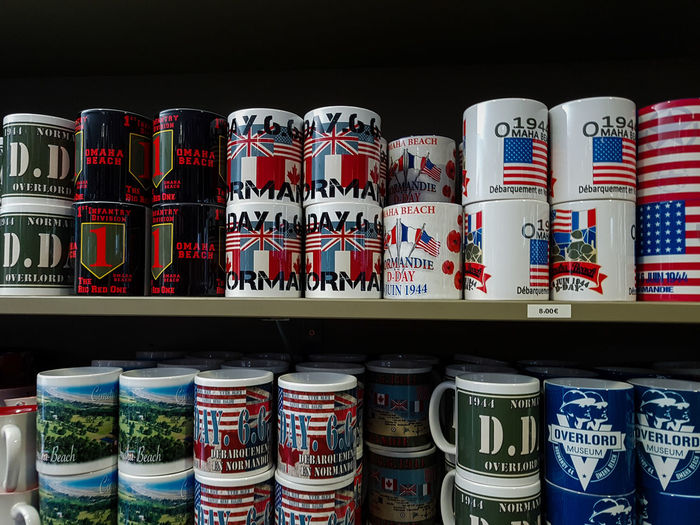 Overlord Museum, Colleville-sur-mer, Normandy, France, July 2017 D-Day Operation Overlord Overlord Museum Arrangement Choice Cups For Sale In A Row Large Group Of Objects Multi Colored Museum Overlord Shelf Souvenirs Souvenirshop Variation