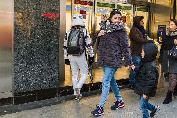 A young boy looking at a street performer dressed as storm trooper entering the Metro in Madrid. City Life Metro Stormtrooper Boy Candid Casual Clothing City City Life Day Editorial  Expression Full Length Public Transportation Real People Standing Togetherness Transportation Women