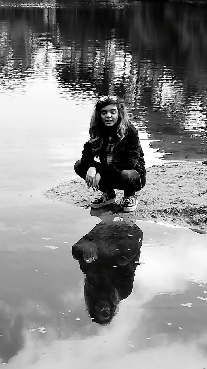water, reflection, young women, young adult, real people, lake, waterfront, one person, looking at camera, portrait, full length, lifestyles, outdoors, day, front view, leisure activity, beautiful woman, nature, smiling, happiness, sitting, warm clothing