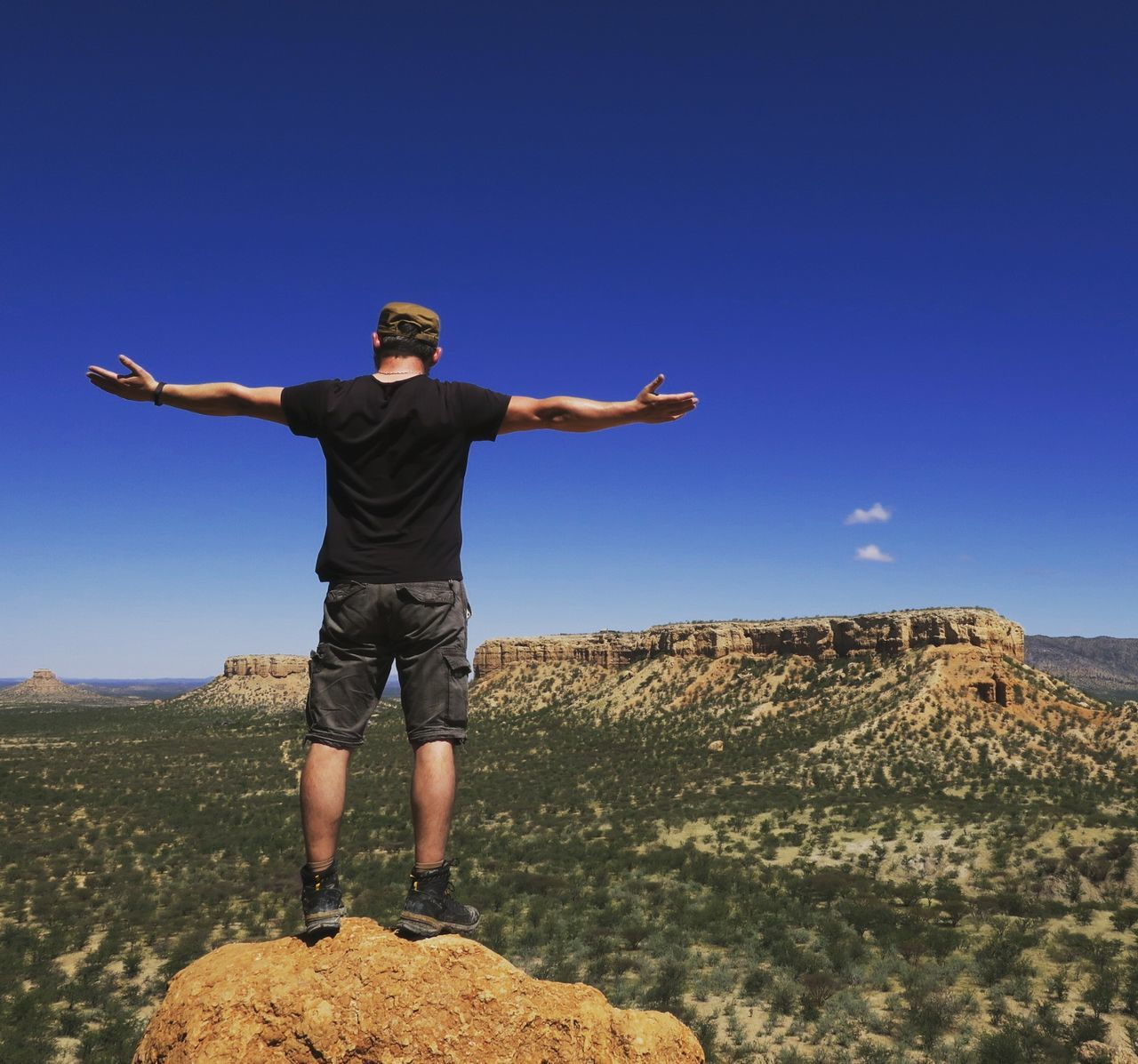 Rear View Of Man With Arms Outstretched Standing On Cliff Against Sky