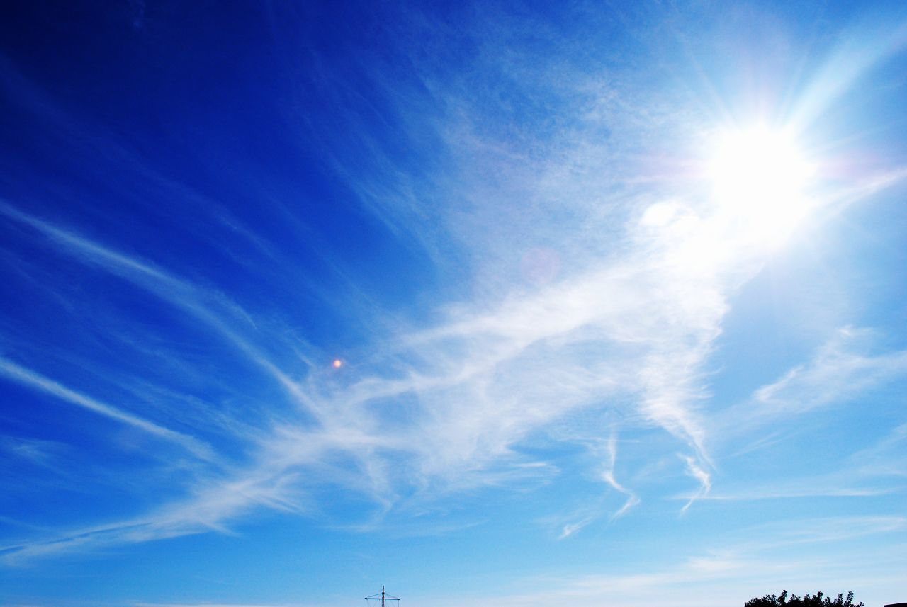 sunbeam, sky, sun, blue, sunlight, low angle view, lens flare, beauty in nature, scenics, nature, tranquility, cloud - sky, day, tranquil scene, outdoors, no people, vapor trail