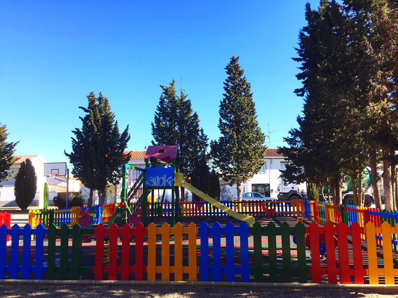 Urban Adapted To The City Tree Outdoors Multi Colored Building Exterior Architecture Day Sky No People Color Palette Street (null) Colours Tranquility Color Colorful Park - Man Made Space Park Multicolors  Playground From My Point Of View Wooden Fence Tranquil Scene Cityscape