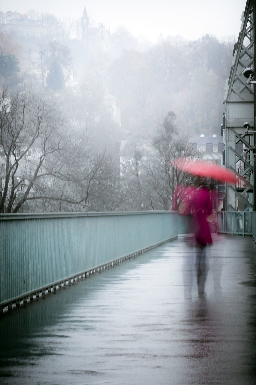 Blurred Motion Of Woman Walking On Footpath During Rain
