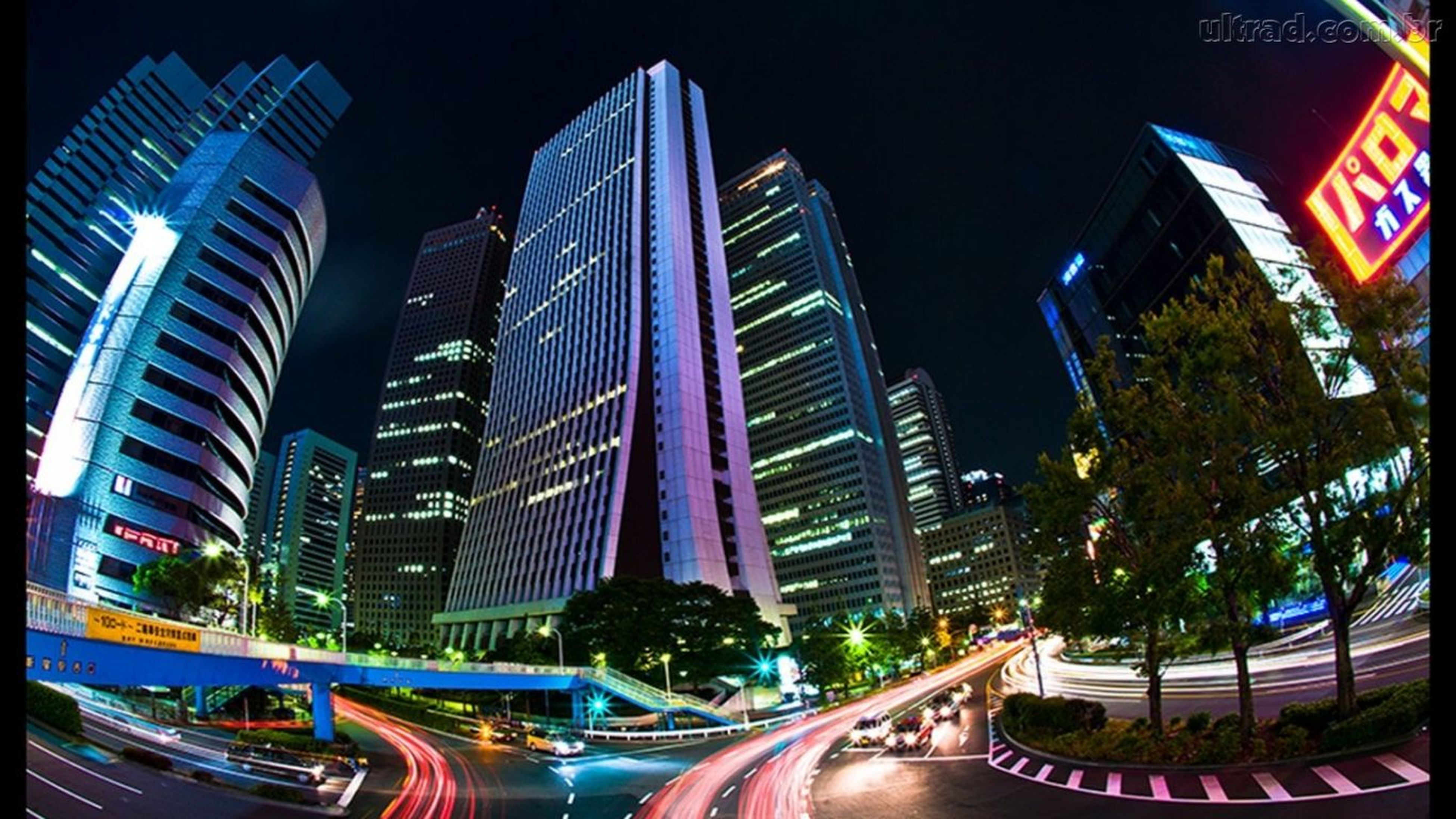 architecture, building exterior, city, built structure, illuminated, modern, skyscraper, night, city life, transportation, office building, tall - high, street, car, sky, low angle view, incidental people, building, road, outdoors