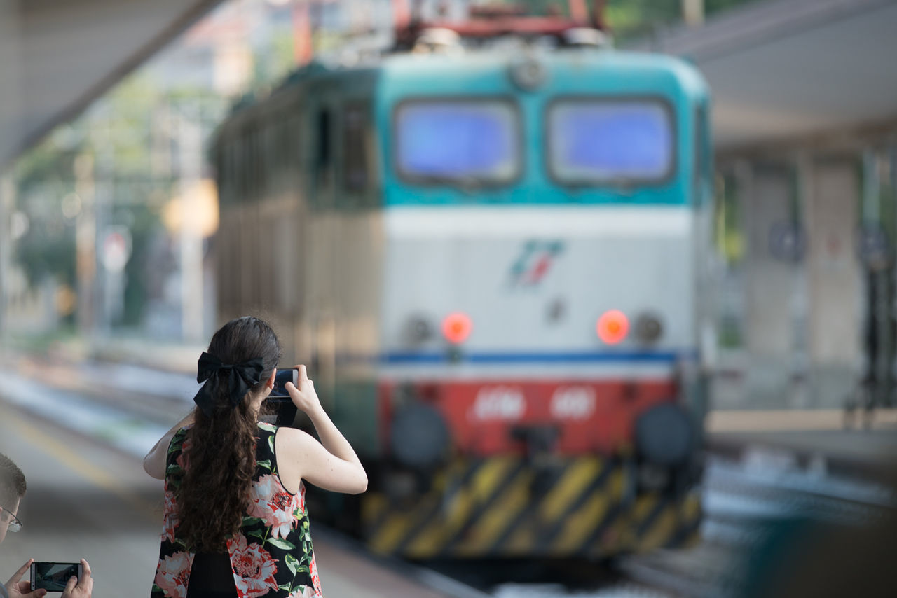 Young woman take a photo of a electric train Electric Train Photography Railway Railwaystation Train Train Station Train Tracks Unrecognizable Person Woman Woman With Camera Young Woman