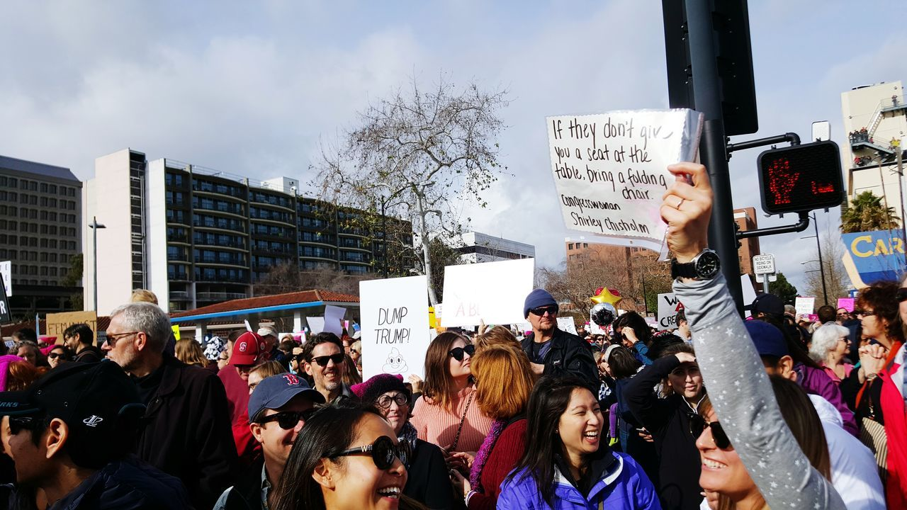 large group of people, real people, protest, men, architecture, women, building exterior, protestor, day, built structure, outdoors, city, crowd, placard, tree, sky, people