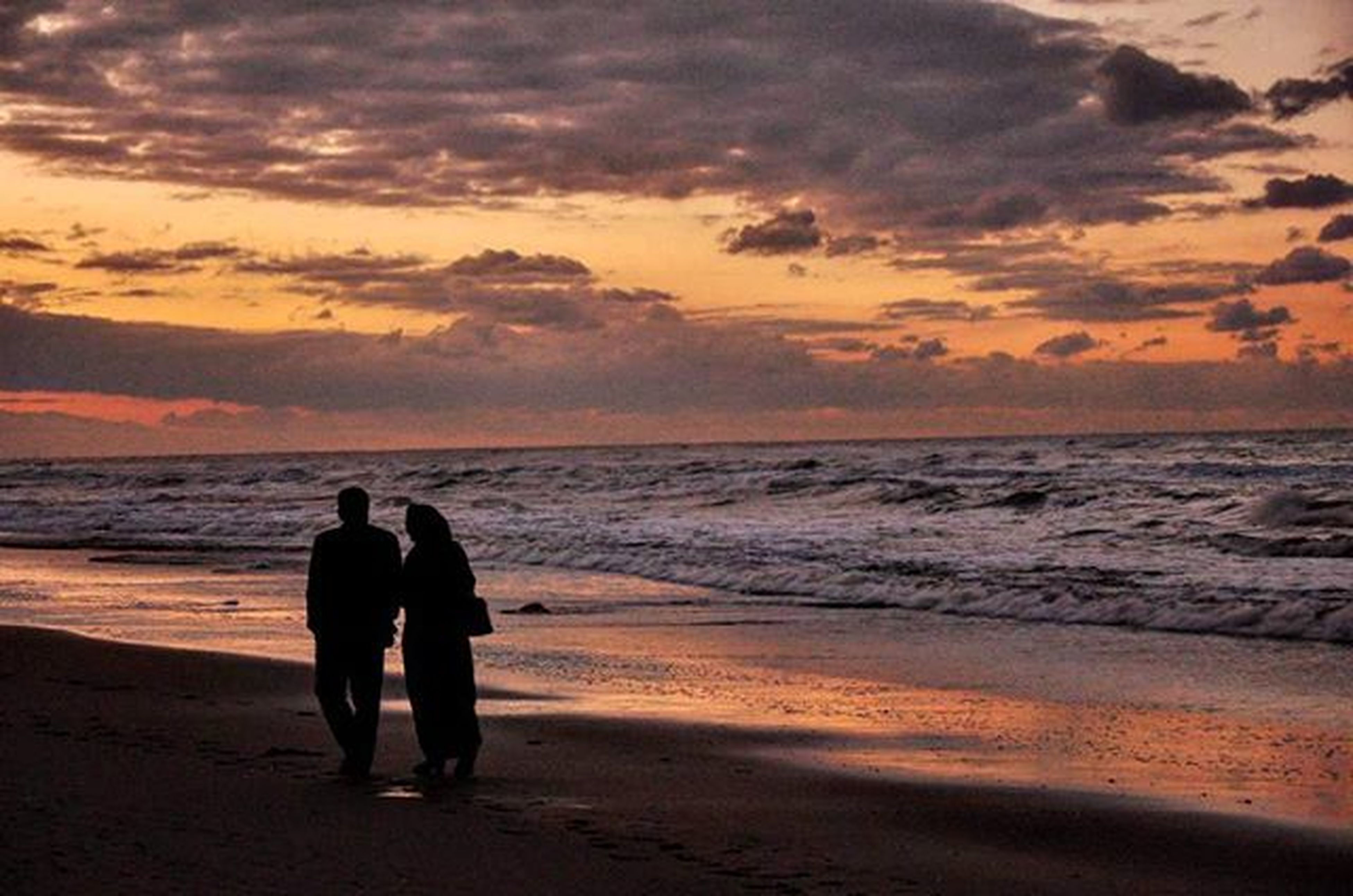 sunset, sea, beach, horizon over water, water, silhouette, sky, shore, scenics, lifestyles, orange color, leisure activity, beauty in nature, men, vacations, cloud - sky, togetherness, tranquil scene