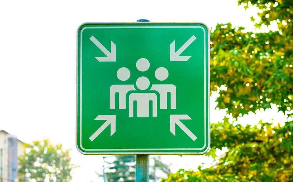 Green assembly point or meeting sign close up in nature. Meeting place for lost people or a safe point in an emergency. Assembly Emergency Meeting Nature Sign Assembly Point Day Human Representation Lost People Outdoors Road Sign Safe Point
