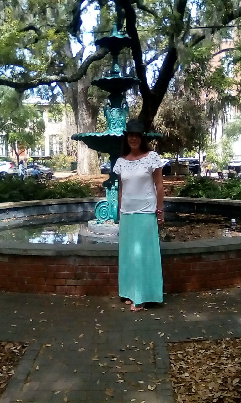 tree, water, real people, leisure activity, lifestyles, one person, casual clothing, full length, front view, day, standing, young women, outdoors, young adult, park - man made space, growth, childhood, nature, statue, happiness, freshness