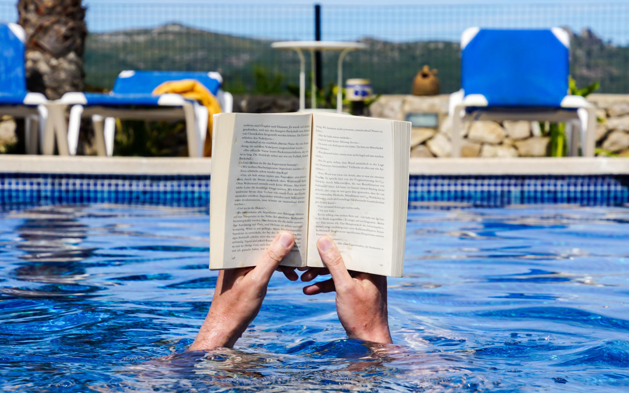 vacation - time to read ;-) Adult Barefoot Blue Book Day Full Length Holding Holiday Leisure Activity Lifestyles Low Section Newspaper One Person Outdoors People Pool Poolside Reading Reading A Book Real People Relaxing Swimming Pool Water Live For The Story BYOPaper! The Photojournalist