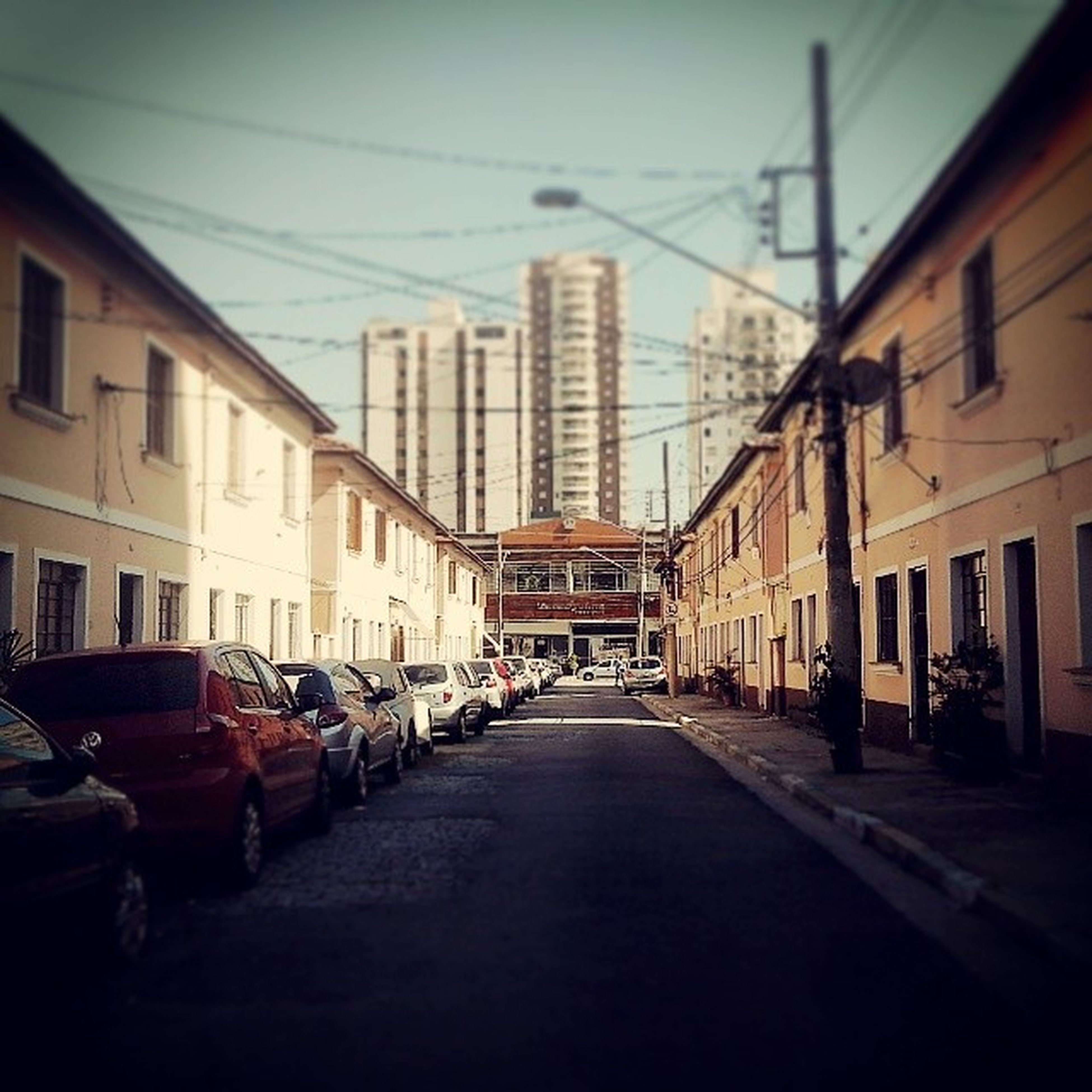 building exterior, architecture, built structure, transportation, city, street, car, the way forward, land vehicle, mode of transport, residential structure, building, diminishing perspective, residential building, road, sky, city life, city street, incidental people, in a row