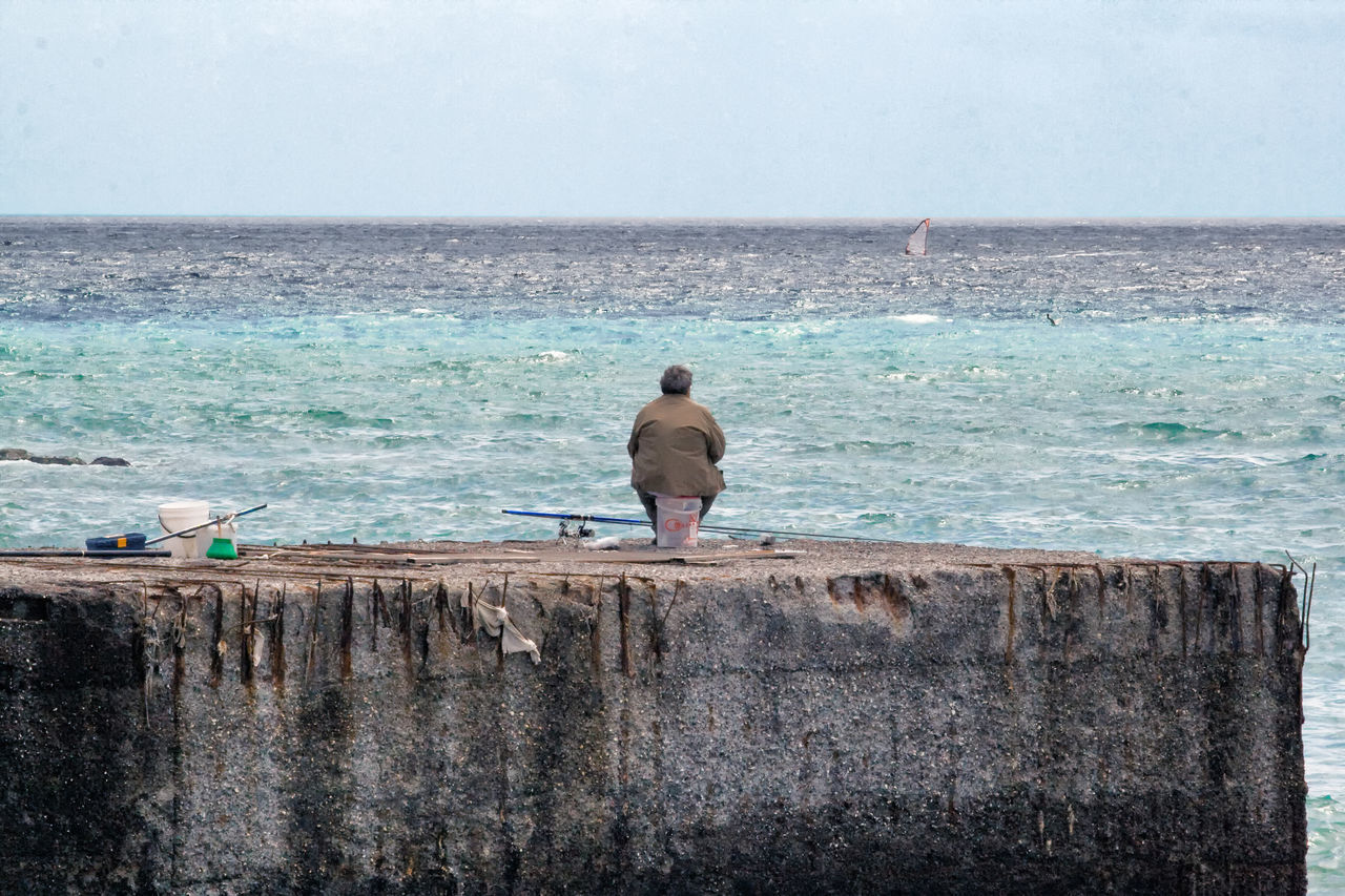 Lonely fisherman on the dock Alone Time Animal Wildlife Animals In The Wild Beach Beauty In Nature Bird Day Fisherman Horizon Over Water Loliness Mammal Men Nature Outdoors Perching Rear View Scenics Sea Sky Water