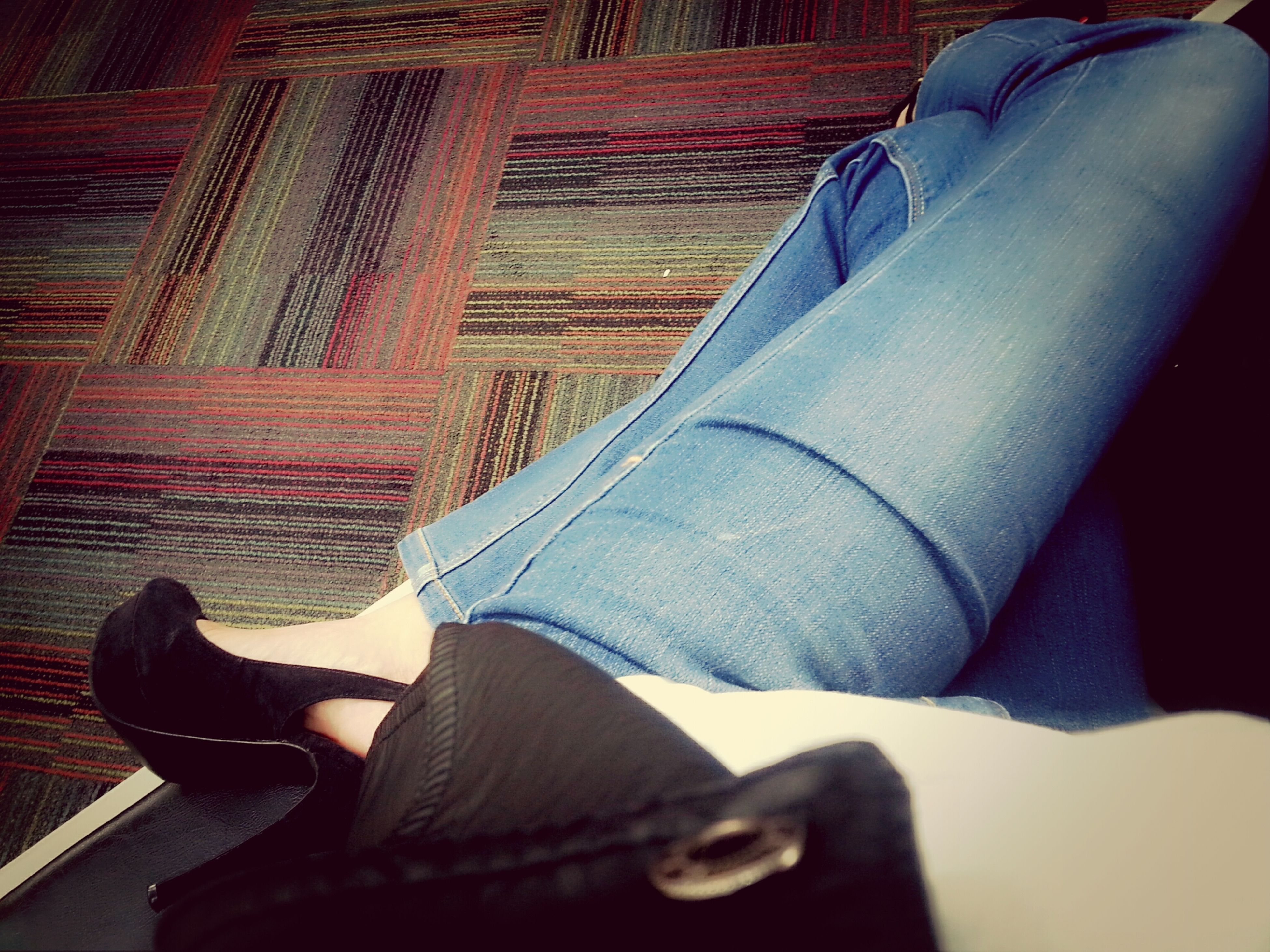 low section, lifestyles, person, indoors, leisure activity, sitting, shoe, casual clothing, relaxation, men, high angle view, personal perspective, jeans, standing, human foot