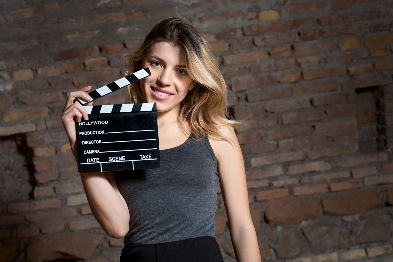 Young blonde actress smiling with movie clapper board Actress Audition Beautiful Blonde Brick Wall Cinema Clapboard Clapper Clapper Board Clapperboard Film Girl Looking At Camera MOVIE People Pretty Smiling Woman Young
