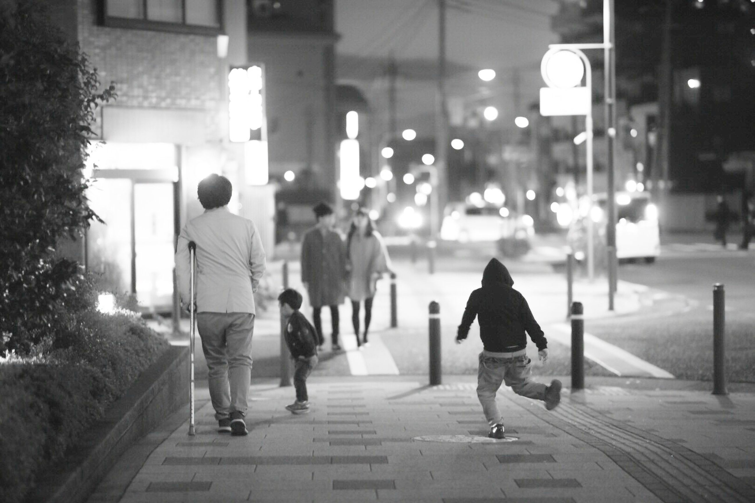 walking, real people, rear view, full length, focus on foreground, street, illuminated, lifestyles, outdoors, city life, night, leisure activity, women, men, togetherness, built structure, city, building exterior, warm clothing, adult, people