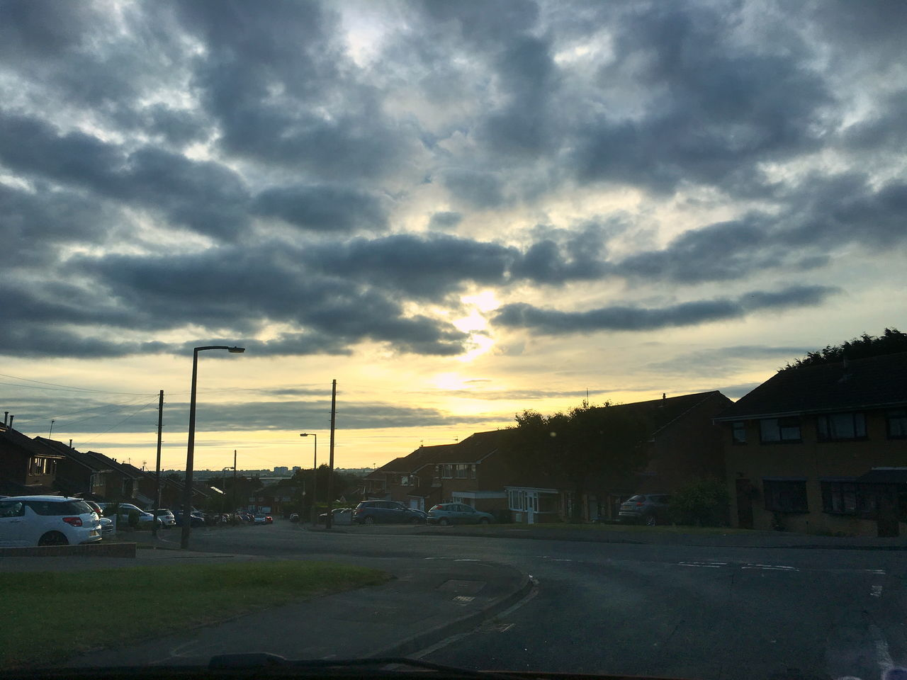 sky, cloud - sky, car, transportation, sunset, dramatic sky, road, land vehicle, built structure, building exterior, street light, no people, mode of transport, architecture, electricity pylon, outdoors, nature, tree, city, day