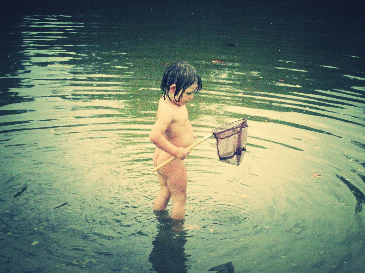 Naked Child With Fishing Net Standing In Lake