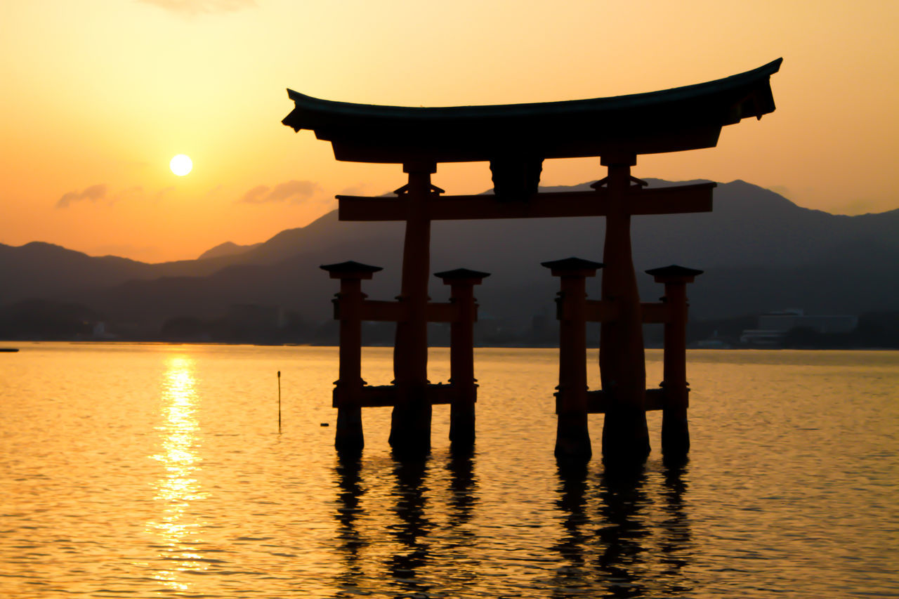 Miyajima gate (new edit) Gate Japan Japan Photography Japanese Culture Japanese Shrine Japanese Style Japanese Temple Japanese Traditional Mountain Range Nature Ocean Orange Color Outdoors Real People Reflection Reflections In The Water Sea Silhouette Sky Sun Sunset Tree Water