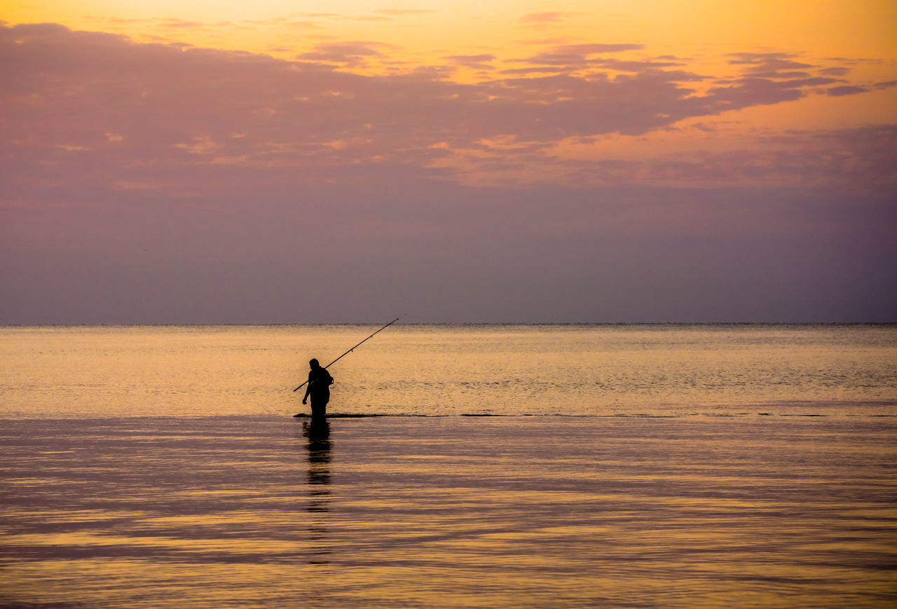 sea, sunset, water, nature, horizon over water, fishing, beauty in nature, one person, scenics, silhouette, real people, standing, outdoors, tranquil scene, men, weekend activities, sky, waterfront, fishing pole, tranquility, oar, paddleboarding, day, people