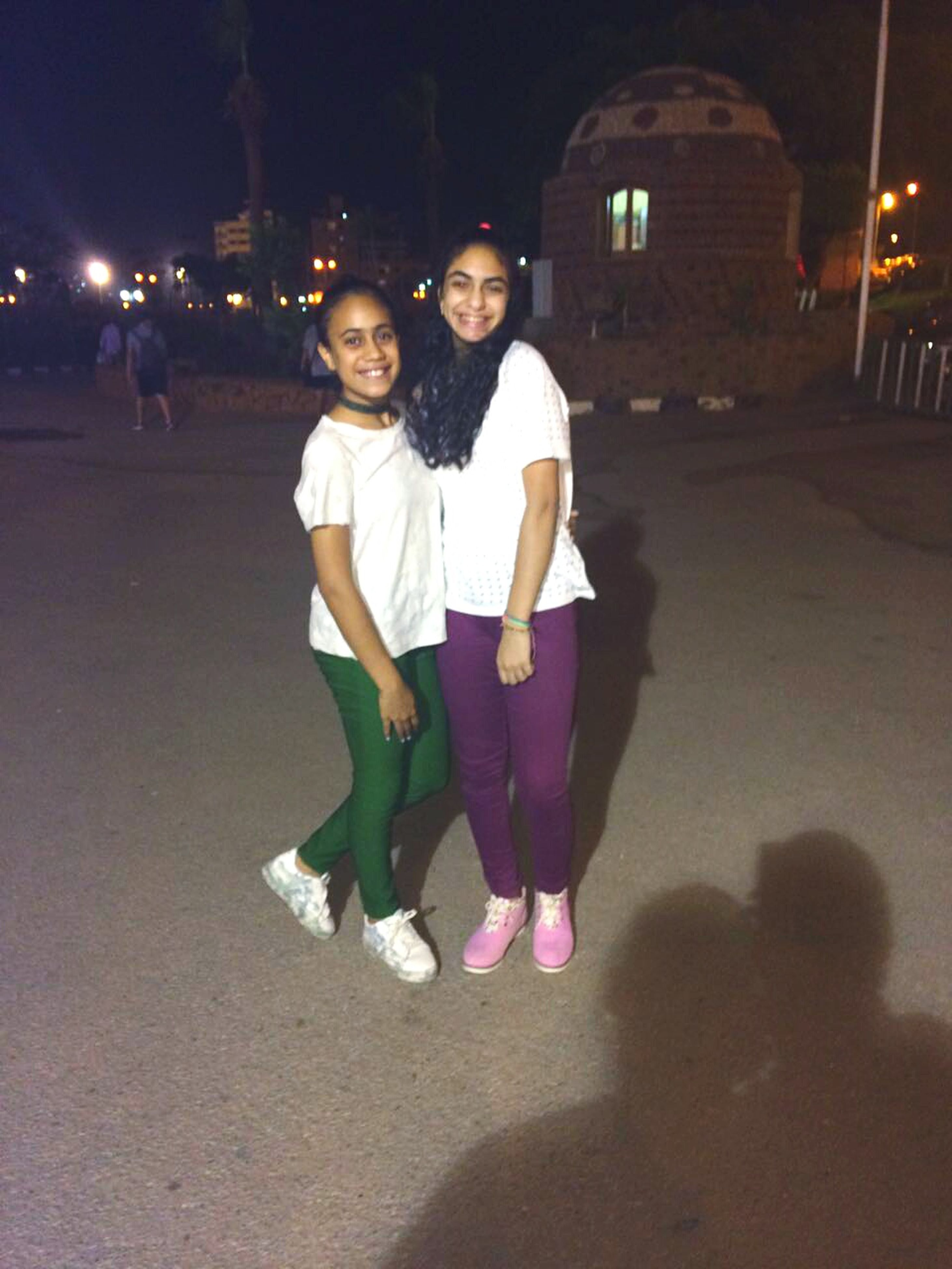full length, looking at camera, night, togetherness, smiling, happiness, lifestyles, real people, portrait, illuminated, two people, front view, love, outdoors, leisure activity, young adult, building exterior, architecture, young women, built structure, standing, bonding, cheerful, city, friendship, people, adult