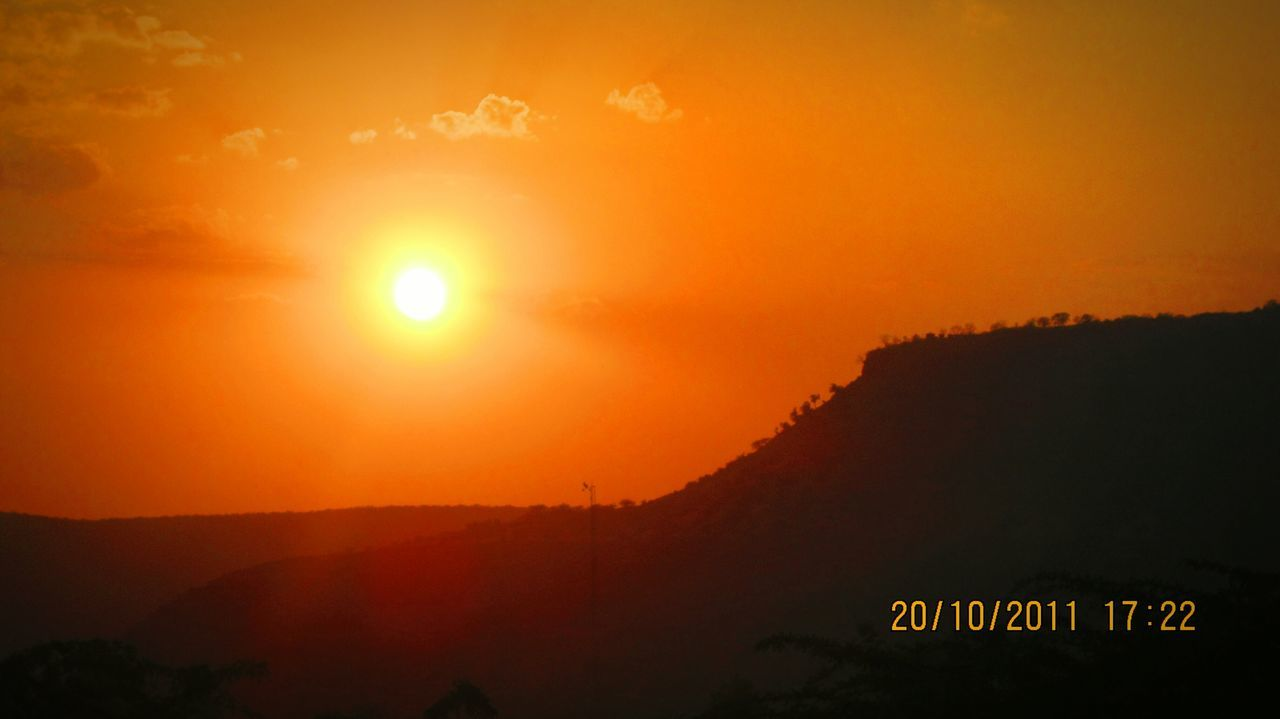 sunset, sun, orange color, nature, beauty in nature, sky, outdoors, scenics, mountain, text, communication, silhouette, sunlight, no people, tranquil scene, tranquility, day