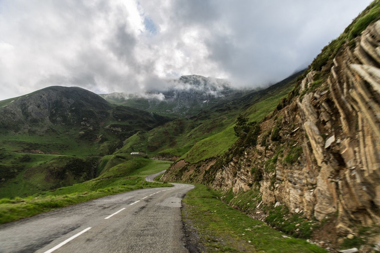 Road Amidst Mountains Against Cloudy Sky