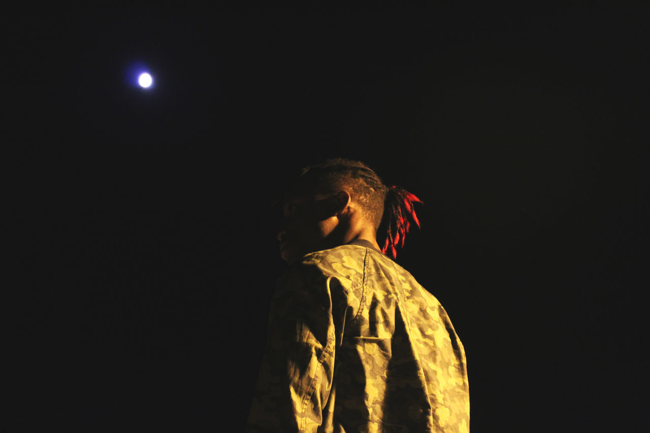 night, copy space, illuminated, black background, low angle view, studio shot, standing, real people, lifestyles, one person, outdoors, clear sky, young adult, halloween, sky, people
