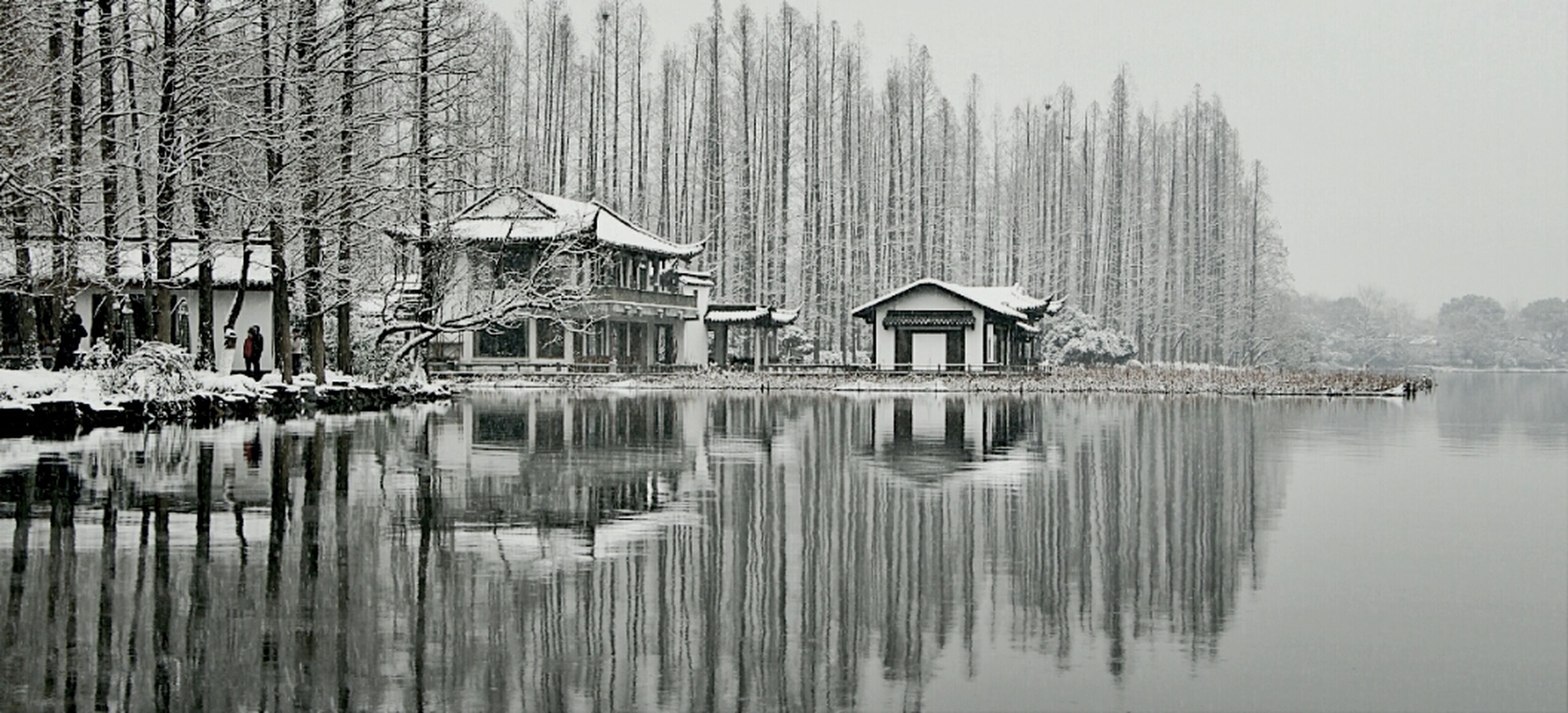 winter, snow, cold temperature, water, built structure, tree, building exterior, architecture, reflection, lake, waterfront, season, tranquility, tranquil scene, nature, weather, river, scenics, frozen, beauty in nature